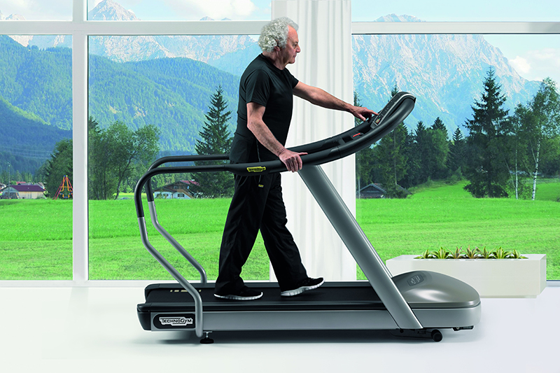a senior citizen working out using a Technogym machine