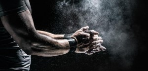 An athlete dusting his hands to avoid accidents in the gym.