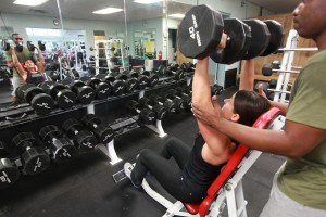 Trainer with woman lifting weights